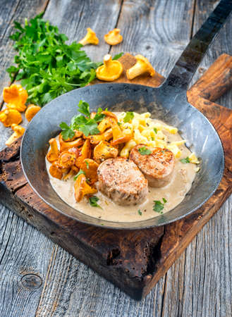 Modern style traditional barbecue pork filet medaillons in cream sauce with chanterelle mushrooms and spaetzle offered as close-up on a rustic wrought iron skillet Фото со стока