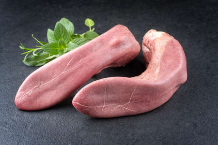 Traditional cooked beef tongue with herbs offered as close-up on a rustic black board