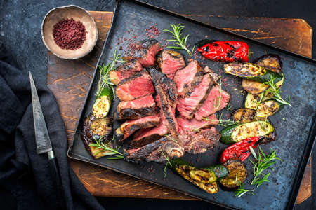 Traditional barbecue dry aged wagyu porterhouse beef steak offered with paprika and eggplant as top view on a rustic metal tray