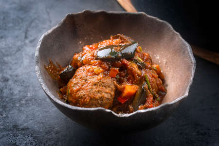 Traditional slow cooked American Tex Mex meatballs with eggplant and mincemeat in a spicy sauce offered as close-up in a rustic design bowl