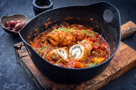 Modern style traditional slow cooked Italian veal roulades saltimbocca with vegetable and olives in spicy gravy sauce as close-up in a design pot