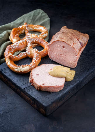 Traditional oven-fresh Bavarian leberkaese sliced and as piece served with pretzels and hot mustard as close-up on an old rustic wooden board