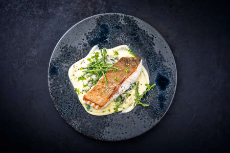 Modern style traditional fried skrei cod fish filet with mashed potatoes and glasswort served as top view on ceramic design plate with copy space