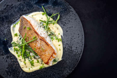 Modern style traditional fried skrei cod fish filet with mashed potatoes and glasswort served as top view on ceramic design plate with copy space right Stock Photo