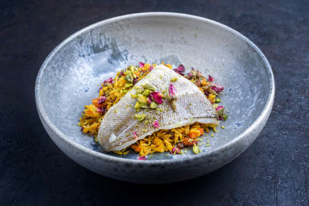 Modern style traditional sauteed skrei cod fish filet with skin in a bed of Persian jeweled saffron rice pilaw served in ceramic design bowl as close-up Фото со стока