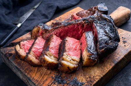 Traditional barbecue dry aged wagyu t-bone beef steak bistecca alla Fiorentina sliced and served with black salt as close-up on an old rustic wooden board