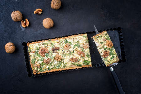 Traditional French Autumn walnut spinach tarte slice served as top view on a rustic backing form on a black board