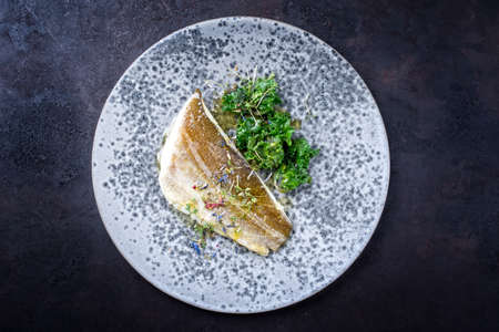 Modern style traditional sauteed skrei cod fish filet with kalette and cress served as top view on ceramic design plate with copy space