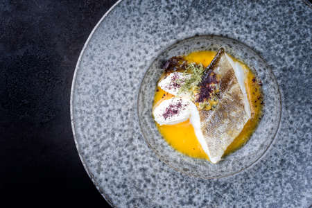 Modern style traditional sauteed skrei cod fish filet with skin with creme fraiche quenelles and algae in passion fruit sauce as top view in ceramic design plate with copy space left Фото со стока