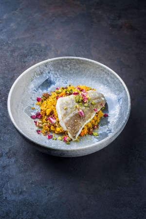 Modern style traditional sauteed skrei cod fish filet with skin in a bed of Persian jeweled saffron rice pilaw served in ceramic design bowl with copy space Фото со стока