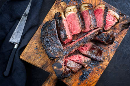 Traditional barbecue dry aged wagyu t-bone beef steak bistecca alla Fiorentina sliced and served with black salt as top view on an old rustic wooden board
