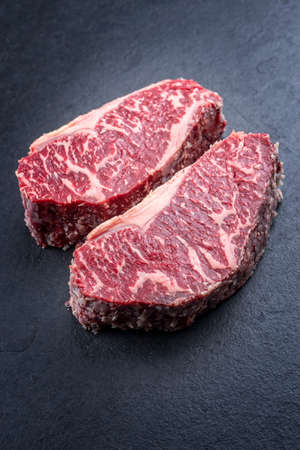 Raw dry aged wagyu roast beef steak offered as close-up on a black board with copy space