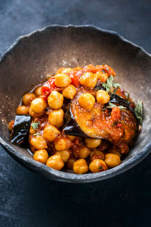 Modern style slow cooked Lebanese vegetarian eggplant stew maghmour served with chickpeas as close-up in a rustic design bowl with copy space on a black board