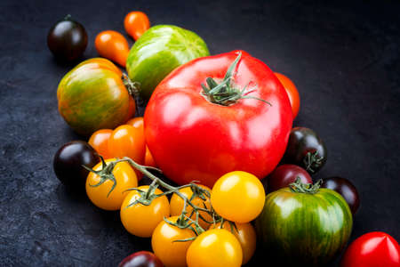 Traditional Italian fresh tomato collection offered as close-up on a rustic black board