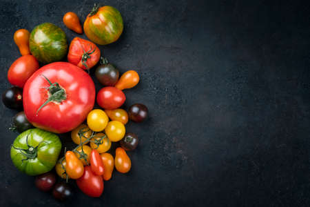 Traditional Italian fresh tomato collection offered as top view on a rustic black board with copy space right
