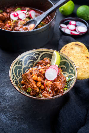 Modern style traditional slow cooked Mexican pozole rojo with tortilla served as close-up in a design bowl on a rustic board Фото со стока