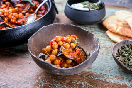 Modern style slow cooked Lebanese vegetarian eggplant stew maghmour served with chickpeas and pita bread as close-up in a rustic design bowl Фото со стока