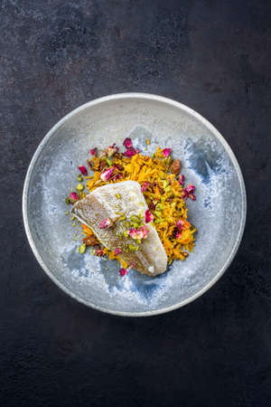 Modern style traditional sauteed skrei cod fish filet with skin in a bed of Persian jeweled saffron rice pilaw served in ceramic design bowl as top view with copy space