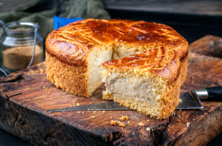 Traditional French gateau basque cake with vanilla cream and pate sablee served as close-up on a rustic wooden board