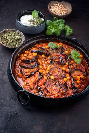 Modern style slow cooked Lebanese vegetarian eggplant stew maghmour served with chickpeas as close-up in a design pot Фото со стока