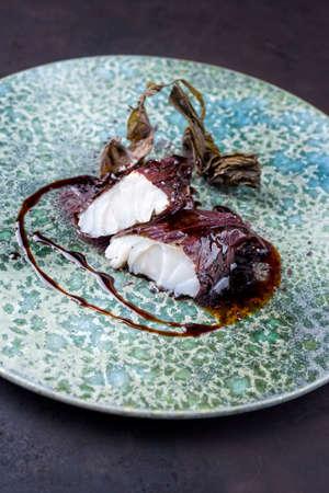 Modern style traditional sauteed skrei cod fish filet with shiso, algae and soy sauce as close-up on ceramic design plate
