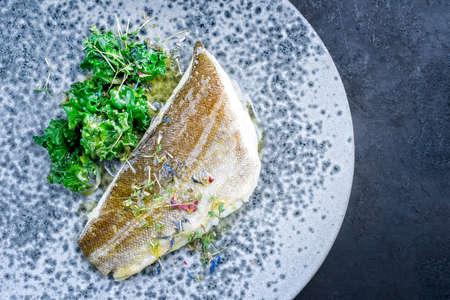 Modern style traditional sauteed skrei cod fish filet with kalette and cress served as top view on ceramic design plate with copy space right
