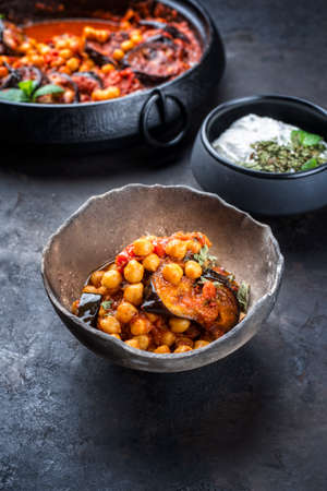 Modern style slow cooked Lebanese vegetarian eggplant stew maghmour served with chickpeas and yoghurt as close-up in a rustic design bowl