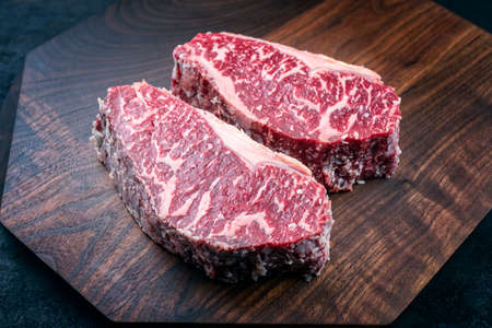 Modern style raw dry aged wagyu roast beef steak offered as top view on a wooden design board