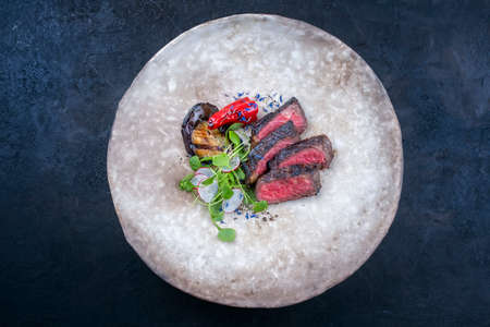 Modern style barbecue dry aged angus roast beef steak natural with vegetable and lettuce served as top view on a rustic design plate with copy space