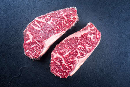 Raw dry aged wagyu roast beef steak offered as top view on a black board with copy space Фото со стока