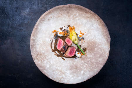 Modern style traditional wild hare back filet braised with fiori di zucchini fritti in game jus served as top view on a rustic design plate with copy space Фото со стока