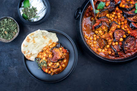 Modern style slow cooked Lebanese vegetarian eggplant stew maghmour served with chickpeas and pita bread as top view in a design pot