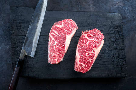 Raw dry aged wagyu roast beef steak offered as top view on a charred wooden board Фото со стока
