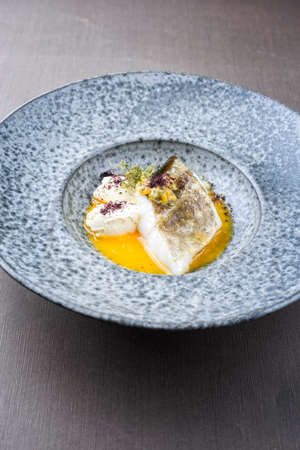Modern style traditional sauteed skrei cod fish filet with skin with creme fraiche quenelles and algae in passion fruit sauce in ceramic design plate as close-up Фото со стока