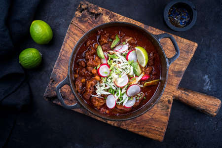 Traditional slow cooked Mexican pozole rojo as top view in a modern design cast-iron roasting dish on an old rustic wooden board