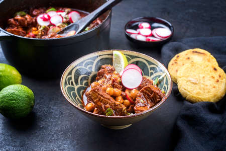 Traditional slow cooked Mexican pozole rojo with tortilla served as top view in a modern design cast-iron roasting dish on a rustic board Фото со стока