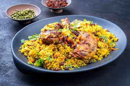 Modern style traditional fried Arabic chicken majboos with chicken leg and jeweled rice served as close-up in a design plate