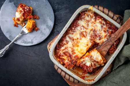Modern style traditional Italian polenta alla sarda con salsiccia with ground meat ragu and pecorino served as top view on a ceramic design backing dish
