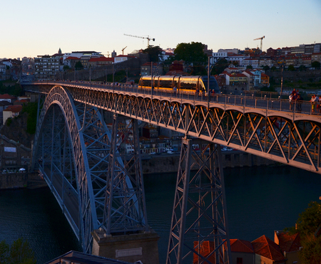 ribeira: Ponte Dom Luís I during sunset, with yellow metro trams - Porto, Portugal