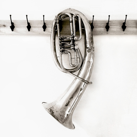 a bent musical wind instrument baritone hangs on a vintage hanger made of wood and metal Stock fotó