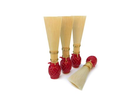 Double reed for bassoon with red thread on a white background. Four mouthpieces for wind musical instruments. With a slight shadow.