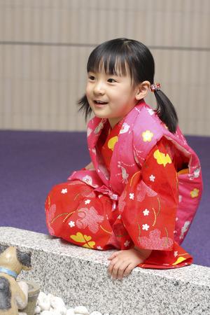 Little girl dress in Japanese Kimono sitting alone by herself