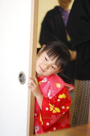 Little girl standing behind the door