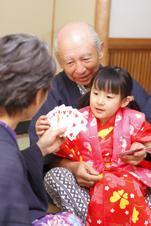 Grandparents playing cards with their granddaughter