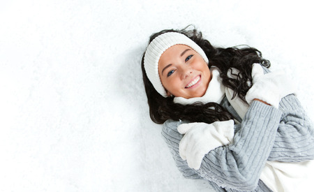 Pretty Caucasian girl in winter clothing laying on a snowy white background.