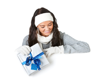 Pretty Caucasian girl in winter clothing, isolated on white behind a white card.
