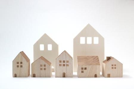 Miniatuur huizen op een witte achtergrond. Bouwstenen geregeld in rij. Stockfoto