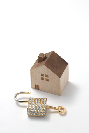 Miniature house and key isolated on white background.