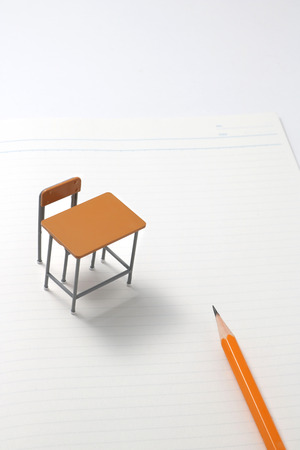 self study: Notebook, pencil and miniature desk. Stock Photo