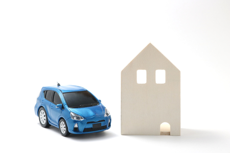 Miniature car and house on white background.